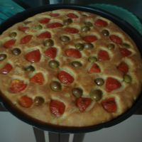 Homemade focaccia with cherry tomatoes and Crudo olives.