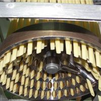Penne being extruded through bronze dies
